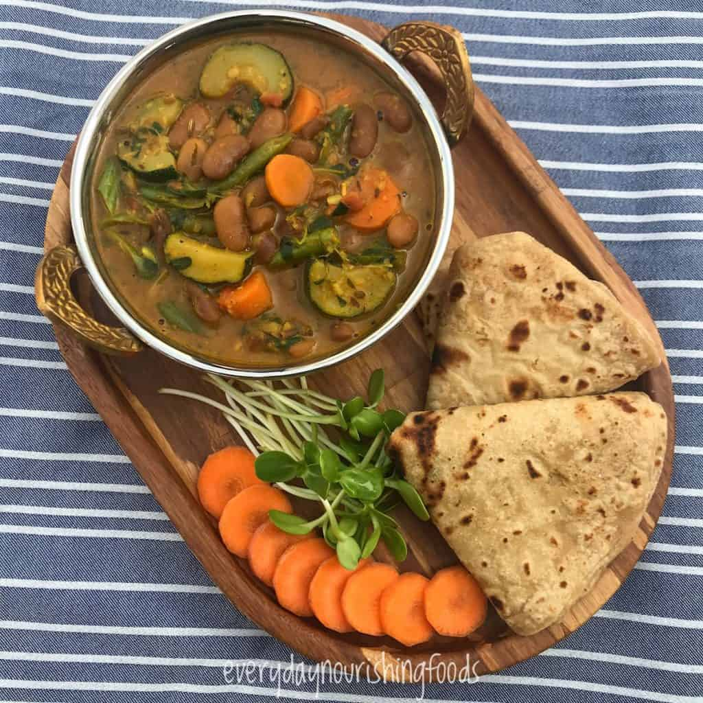 kidney beans curry with salad and whole wheat roti in a plate