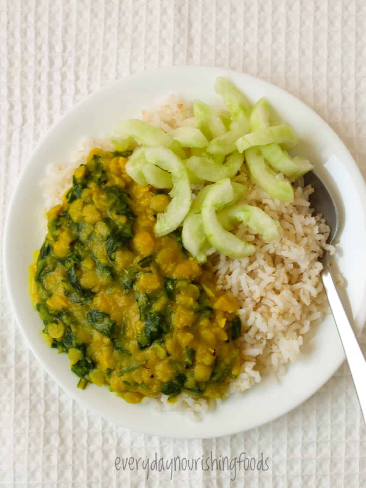 spinach dal with rice and cucumber in a plate